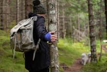 A Hiker Holding Onto A Tree Fo...