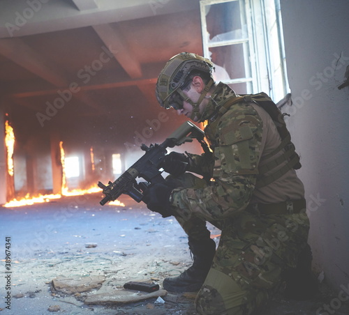 Photo soldier in action near window changing magazine and take cover