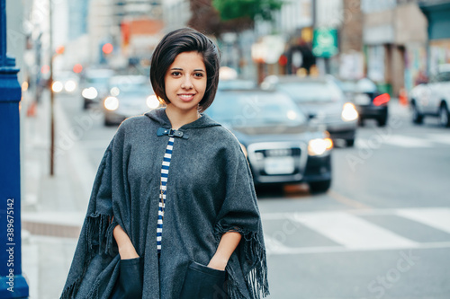 Foto Beautiful Latin young woman in grey stylish poncho with fringe in urban street