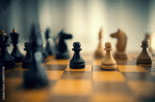 Obraz Wooden chess pieces on the chessboard. - fototapety do salonu