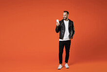 Full Length Of Smiling Young Bearded Man 20s Wearing Basic White T-shirt Black Leather Jacket Standing Using Mobile Cell Phone Typing Sms Message Isolated On Orange Colour Background Studio Portrait.