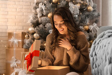Happy Young Woman Opening Christmas Gift At Home. Magic Holiday