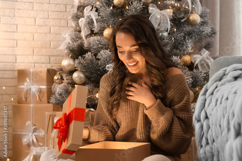 Obraz Happy young woman opening Christmas gift at home. Magic holiday - fototapety do salonu
