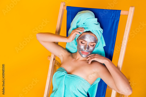Fotografering Photo portrait of sleeping woman with grey face mask laying in blue deck chair i