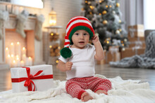 Cute Little Baby With Elf Hat Near Christmas Gift On Floor At Home