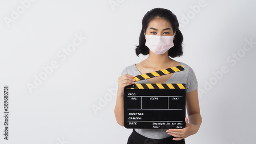 Valokuva Girl or woman wear face mask and hand's holding black clapper board or movie slate use in video production ,film, cinema industry on white background