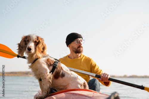 Fotomural Man with a dog in a canoe on the lake