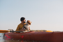 Kayaking With Dogs: Man Sits In A Row Boat On The Lake Next To His Spaniel. Active Rest And Adventures With Pets, Riding A Canoe With Dog