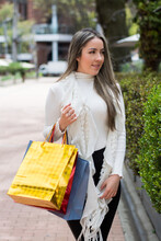 A Woman Walking In The City Streets With Shopping Bags. Woman Shopping