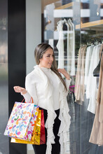 Woman With Shopping Bags Looking At A Shop Display Through The Window