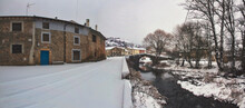 Panoramic Of Snowy Village With Roman Bridge And River
