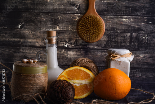 Fototapeta The lay composition with body care products and space for text on dark wood background. a jar of natural cream, a bottle of coconut oil and a ripe orange obraz