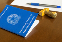 """Brazilian Work Card With Stamp, Pen And Paper On The Table. Employment Contract Concept. Portuguese Text """"Work And Social Security Card"""". Selective Focus."""