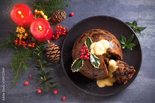 Richly spiced Christmas pudding cake with custard and Christmas decorations Canvas Print