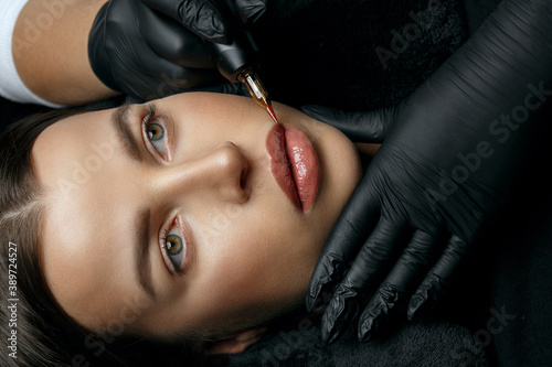 Photo Gorgeous brunette woman having lip permanent