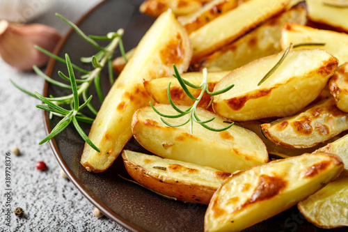 Fototapeta Fresh baked red potatoes with rosemary and garlic on brown plate obraz