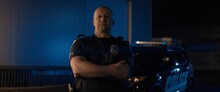 Caucasian Male Police Officer Posing Against Police Car With Flashing Lights At Night. Shot With Anamorphic Lens