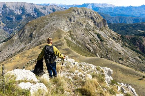 Платно un homme avec un sac à dos avec son chien , face à un panorama en montagne