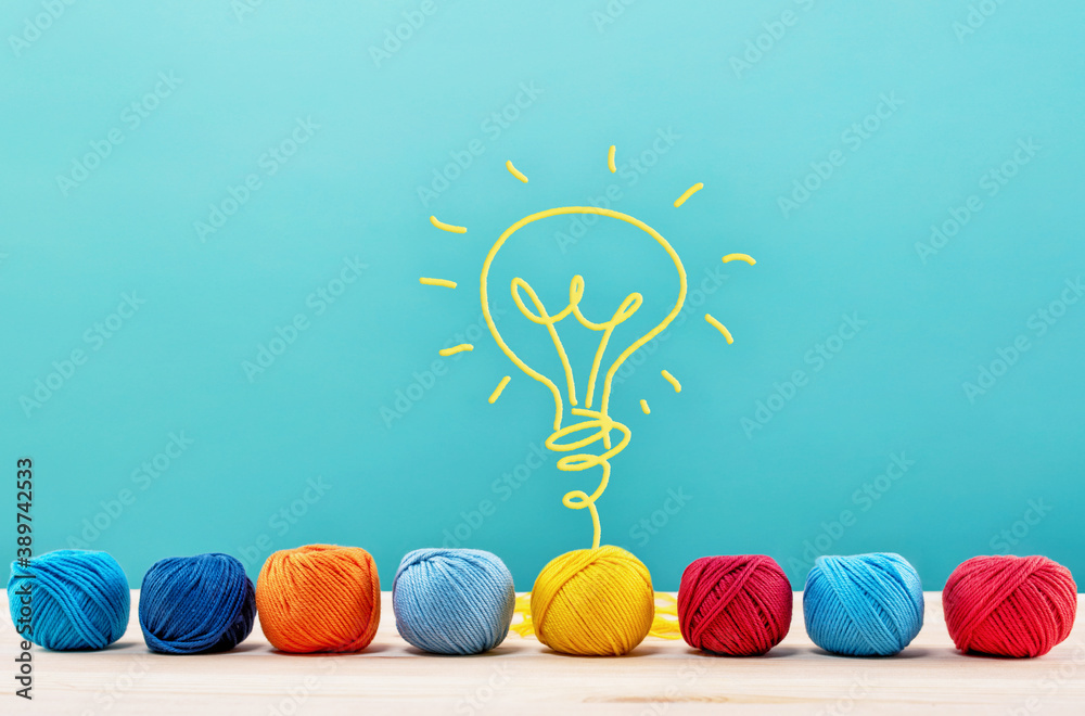 Fototapeta Colored wool balls that do a lightbulb with the wire. Concept of creativity and idea
