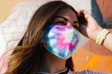 Young Woman Smiling Wearing Tie-dye Mask With Colorful  Urban Mural