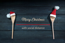 Two Cooking Spoons With Red Santa Claus Hats, Between Them Text Merry Christmas With Social Distance, Dark Blue Wooden Background, Health Safety Concept Against Covid-19 Pandemic