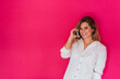 Leinwandbild Motiv Girl with mobile phone on pink