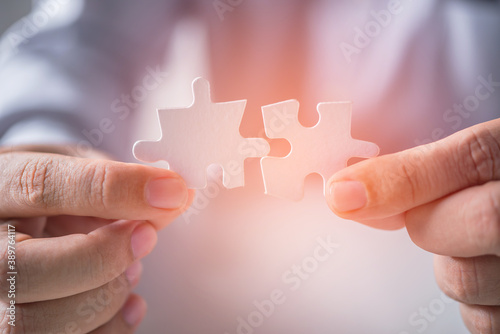 Obraz business man hand connecting jigsaw puzzle pieces - fototapety do salonu