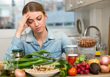 Upset Tired Young Woman Sitting At Home Kitchen Table Full Of Fresh Vegetables