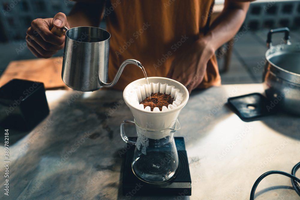Fototapeta Drip coffee, barista pouring water on coffee ground with filter