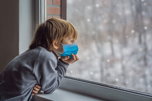 Adorable Kid Boy Sitting Near Window And Looking Outside On Snow On Christmas Day Or Morning Wear Medical Masks Due To The COVID-19 Coronavirus. Smiling Child Fascinated With Snowfall And Big
