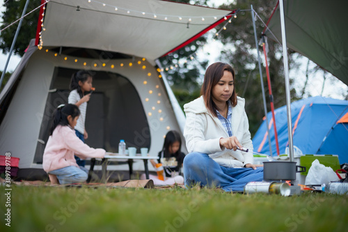 Foto Asian mother cooking for family outside the tent while camping with family in the camping site with happiness