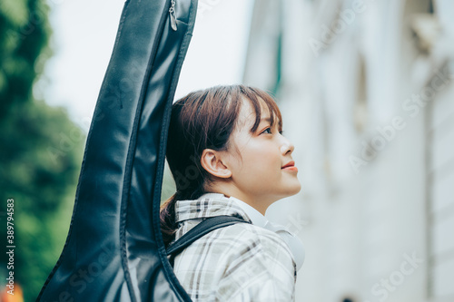 Photo photo of a girl wearing a guitar on her back