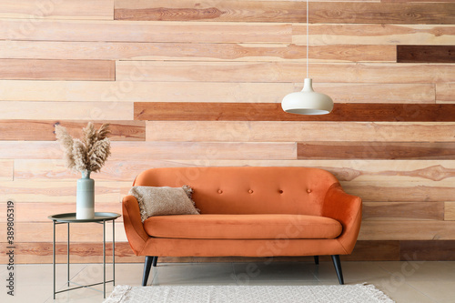Sofa and table near wooden wall