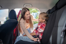 Smiling Mom Fastening Her Daughter's Safety Belt On Backseat Of Car