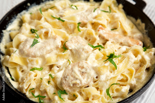 Homemade Chicken Fettuccine Alfredo in a cast-iron pan on a white wooden background, low angle view Wallpaper Mural