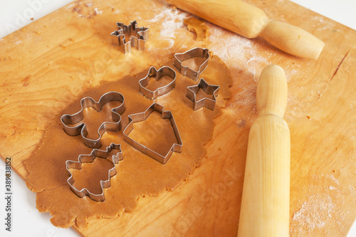 Fotografia Raw dough and rolling pins for Christmas cookies on wooden board