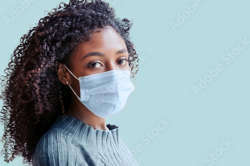 African american girl wearing face mask on background