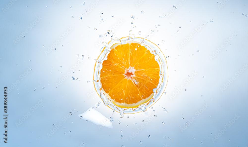 Fototapeta Fresh ripe half of orange fruit splashing into clear water.
