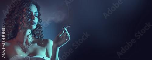 Beautiful smoking young woman, closeup portrait, at night. Beauty fashion sexy model girl with cigarette. Close eyes. Darkness