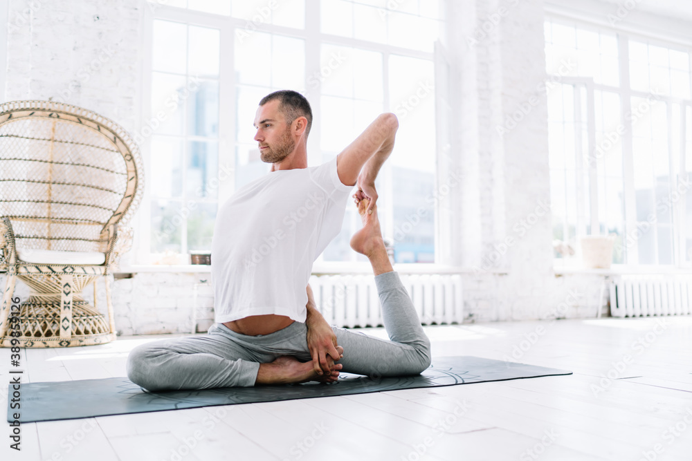 Fototapeta Concentrated male in casual wear doing exercises for stretching muscles feeling recreation and wellness, 20s man enjoying yoga practice in morning at home interior sitting in asana and chilling