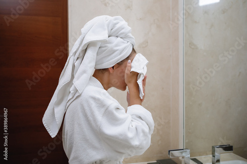 Photo Woman in a white robe and a towel on her head washes in the bathroom