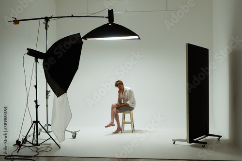 Foto Young barefoot man sits on chair in pose of thinker in photo studio