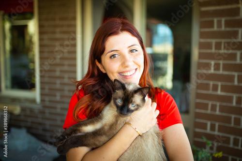 Fényképezés Giovane ragazza sorride con il suo gatto in braccio