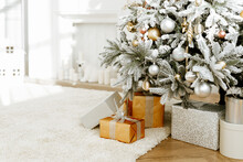 Beautiful Silver And Gold Boxes With Gifts Under The Christmas Tree. New Year And Christmas Holidays Concept.