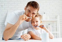 Dad And Little Son Brushing Teeth Together