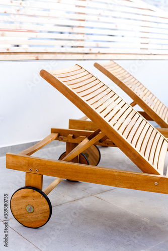 Slika na platnu Wooden chaise lounges sunbed with wheels in patio