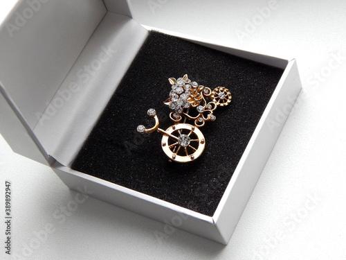 Billede på lærred golden brooch in the form of a bicycle in box