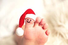 Child Big Toe With Santa Hat And Smiling Face.  Closeup Photo Of Caucasian Foot. Christmas And Barefoot Concept With Copy Space.