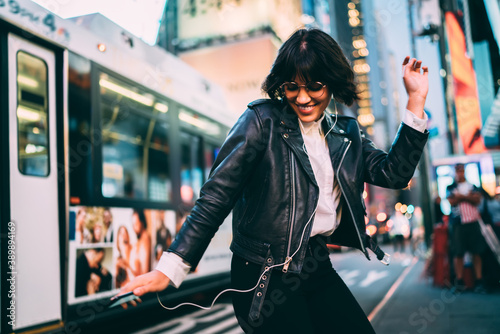 Obraz Carefree woman in fashionable clothing listening funny audio and dancing during evening walk in New York City, cheerful female enjoying adolescent music podcast during nightlife lifestyle in Manhattan - fototapety do salonu