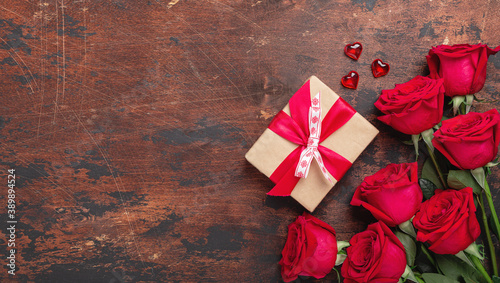 Red roses, gift box and decorative hearts on wooden background. Valentine's day horizontal banner
